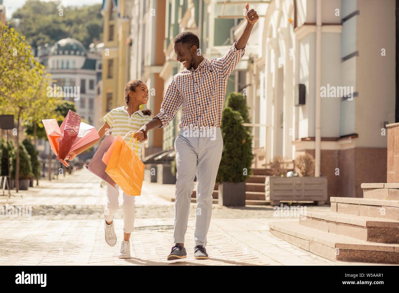 Heureux l'homme à la peau sombre balade avec sa fille Banque D'Images
