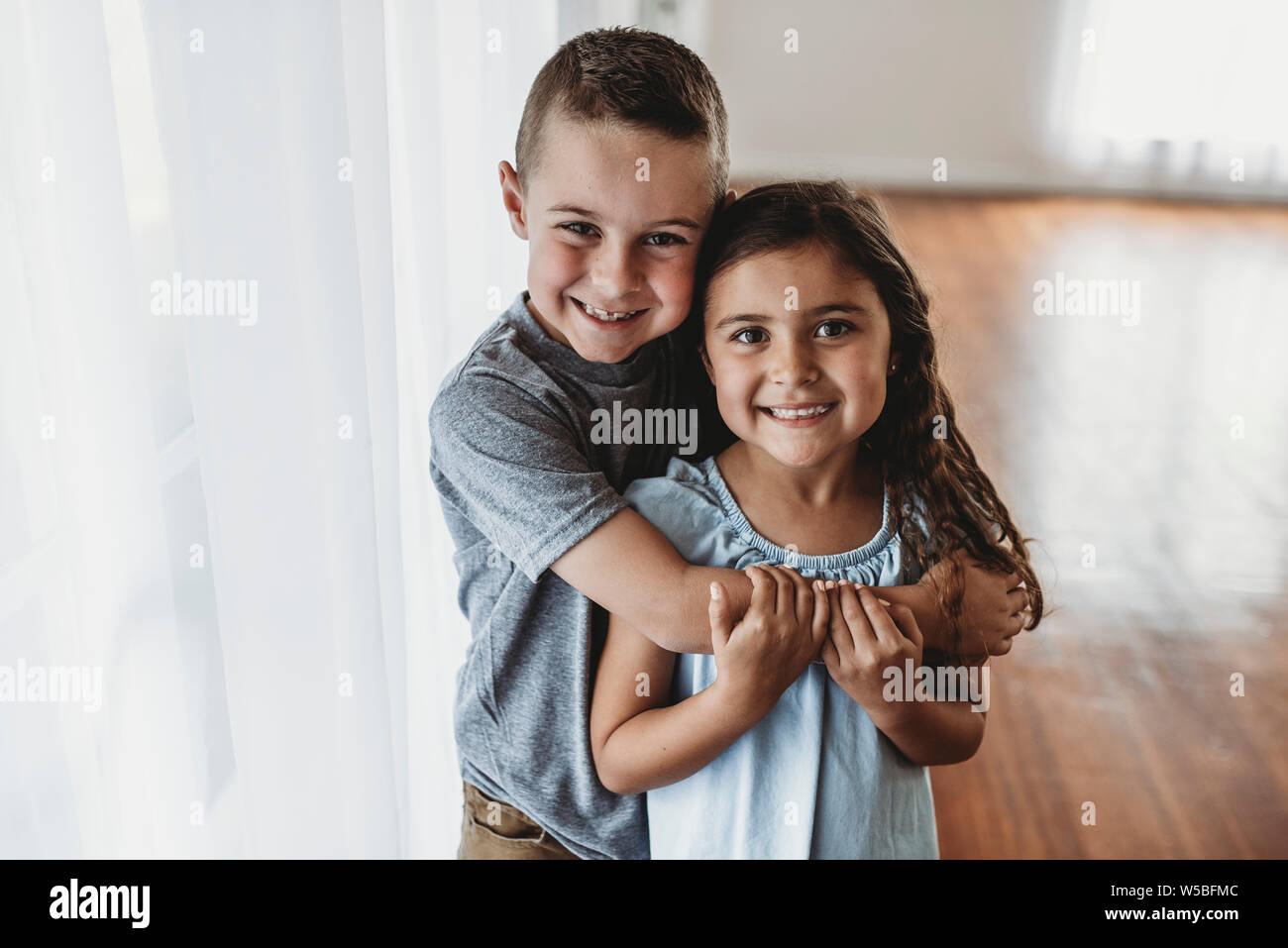 Frère et sœur, joignant en lumière naturelle studio Banque D'Images