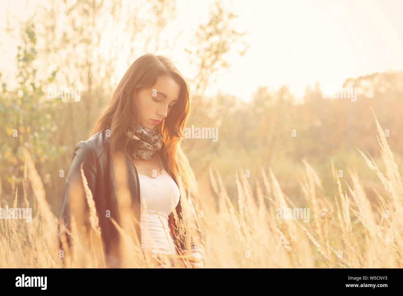Belle jeune femme triste marche à l'herbe sèche à la bas Banque D'Images