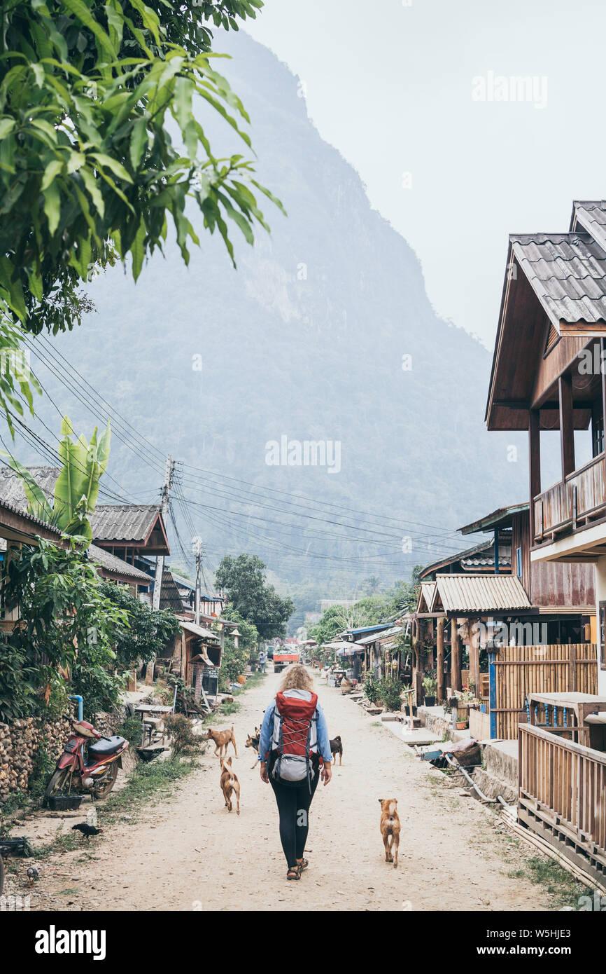 Young Caucasian woman with backpack marche sur la rue centrale du village de Muang Ngoi, Laos, accompagné de chiens errants. Orientation verticale Banque D'Images