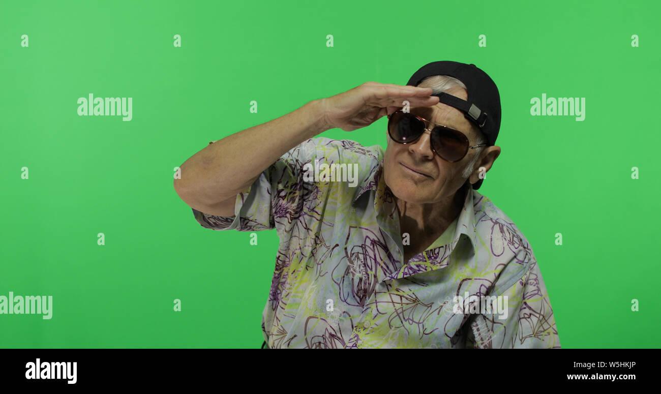 Man'en lunettes de regarder quelque chose. Beau vieil homme sur fond d'incrustation. Grand-père âgé en chemise colorée. Place pour votre logo ou texte. Arrière-plan de l'écran vert Banque D'Images