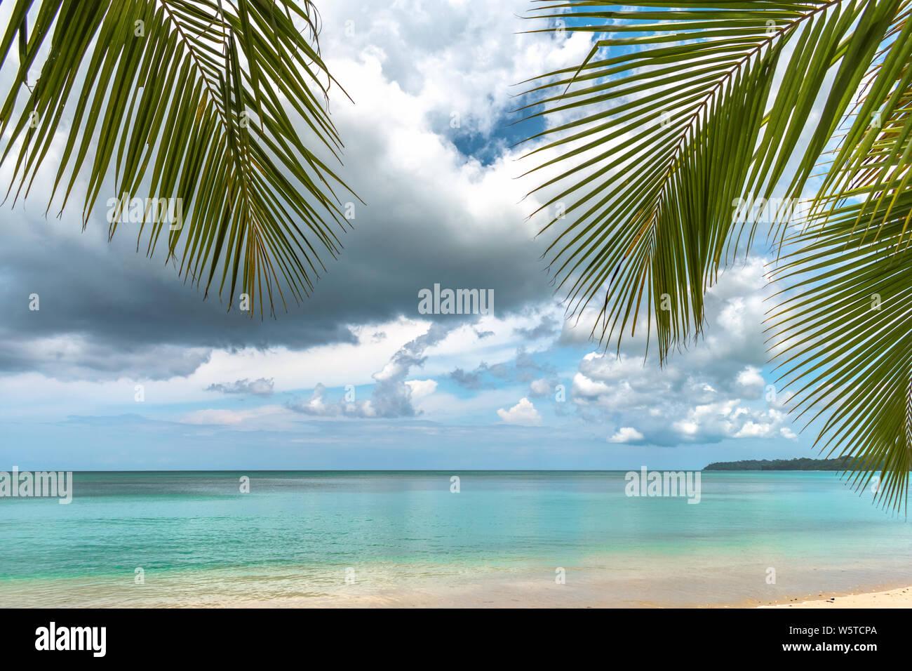 Littoral tranquille tropical de l'île à distance par jour nuageux avec plage vierge naturel avec l'eau peu profonde de couleur turquoise, Horizon dégagé. Banque D'Images