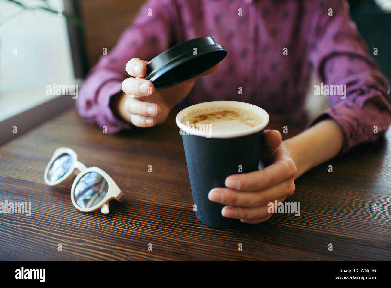 Les mains avec une tasse de Cappuccino, avec mousse épaisse à emporter en noir en papier. Banque D'Images