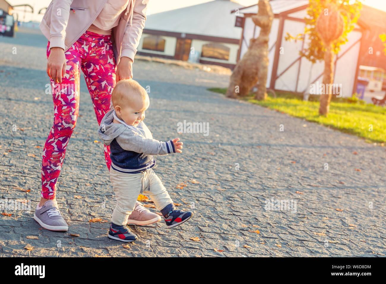 Jolie petite blonde adorable bébé garçon faire les premières étapes avec le soutien aux mères au parc de la ville à l'heure du coucher du soleil en soirée. Happy funny enfant l'apprentissage de la marche Banque D'Images