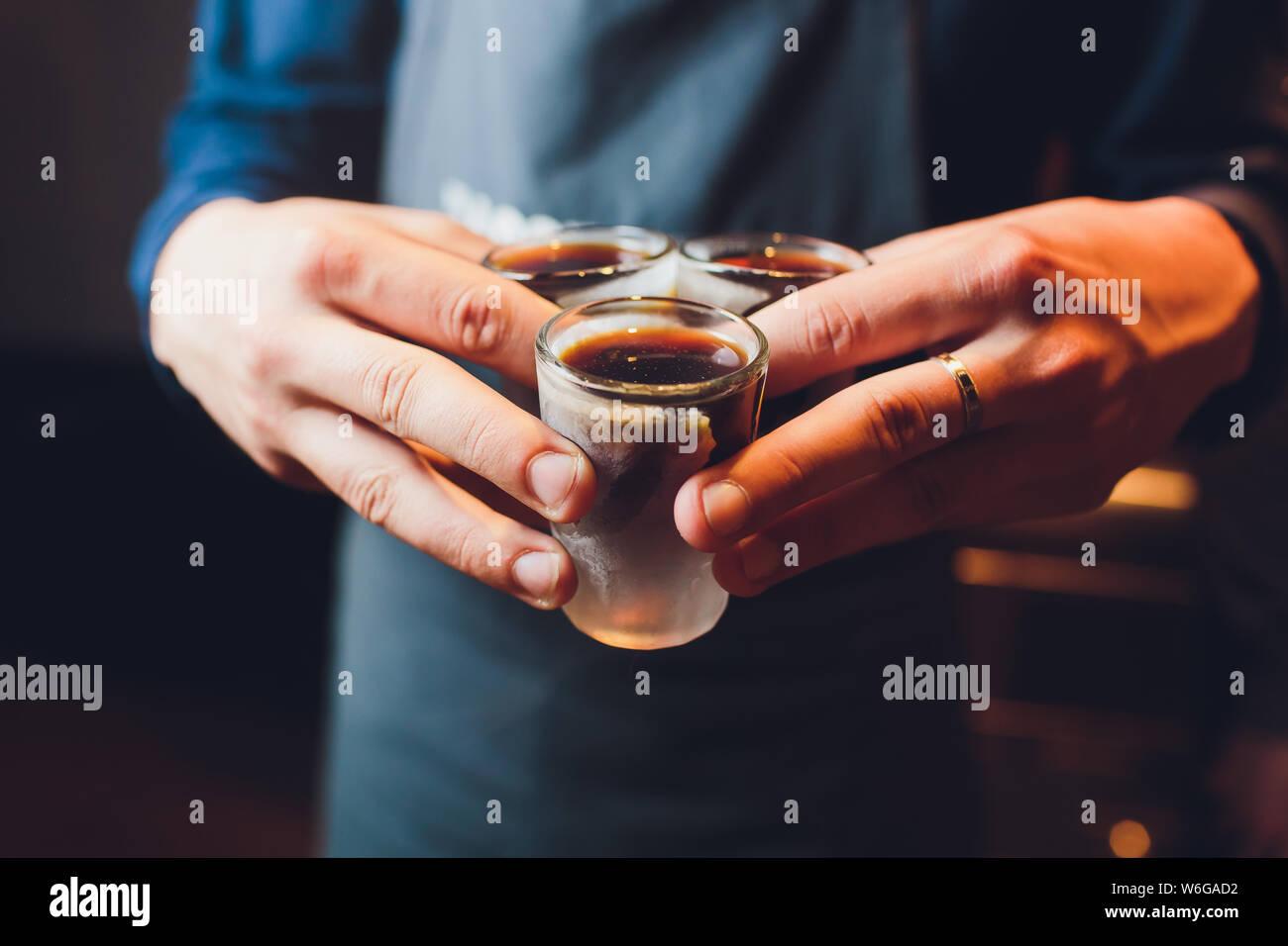 Cheer main d'hommes avec des lunettes de tir ou liqueur. Les amis boire shot ou de liqueur et des acclamations. Bravo à mains mâles sur arrière-plan de la barre d'alcool trouble Banque D'Images