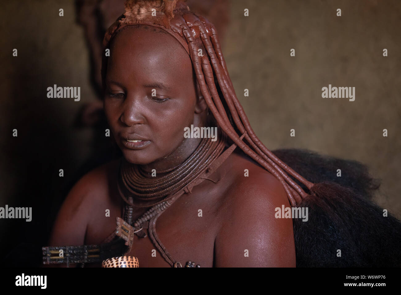 Opuwe, Namibie - Juillet 12, 2019: Une tribu Himba traditionnel portrait femme sombre dans sa cabane de torchis. Banque D'Images