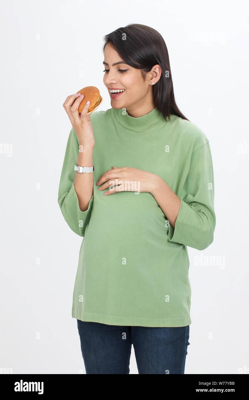 Pregnant woman eating hamburger Banque D'Images