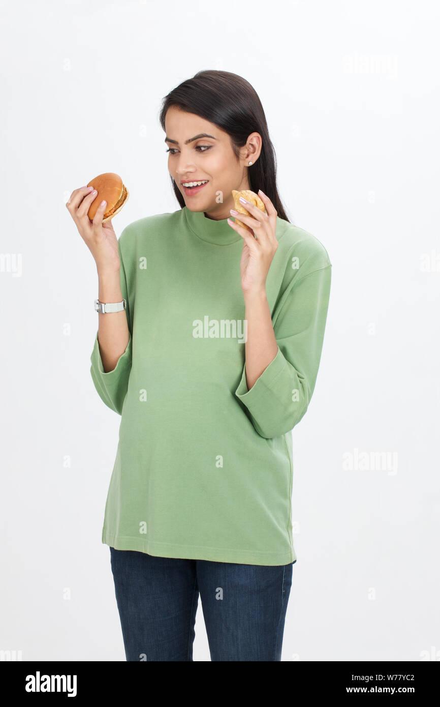 Femme enceinte qui mange du hamburger et de la samosa Banque D'Images