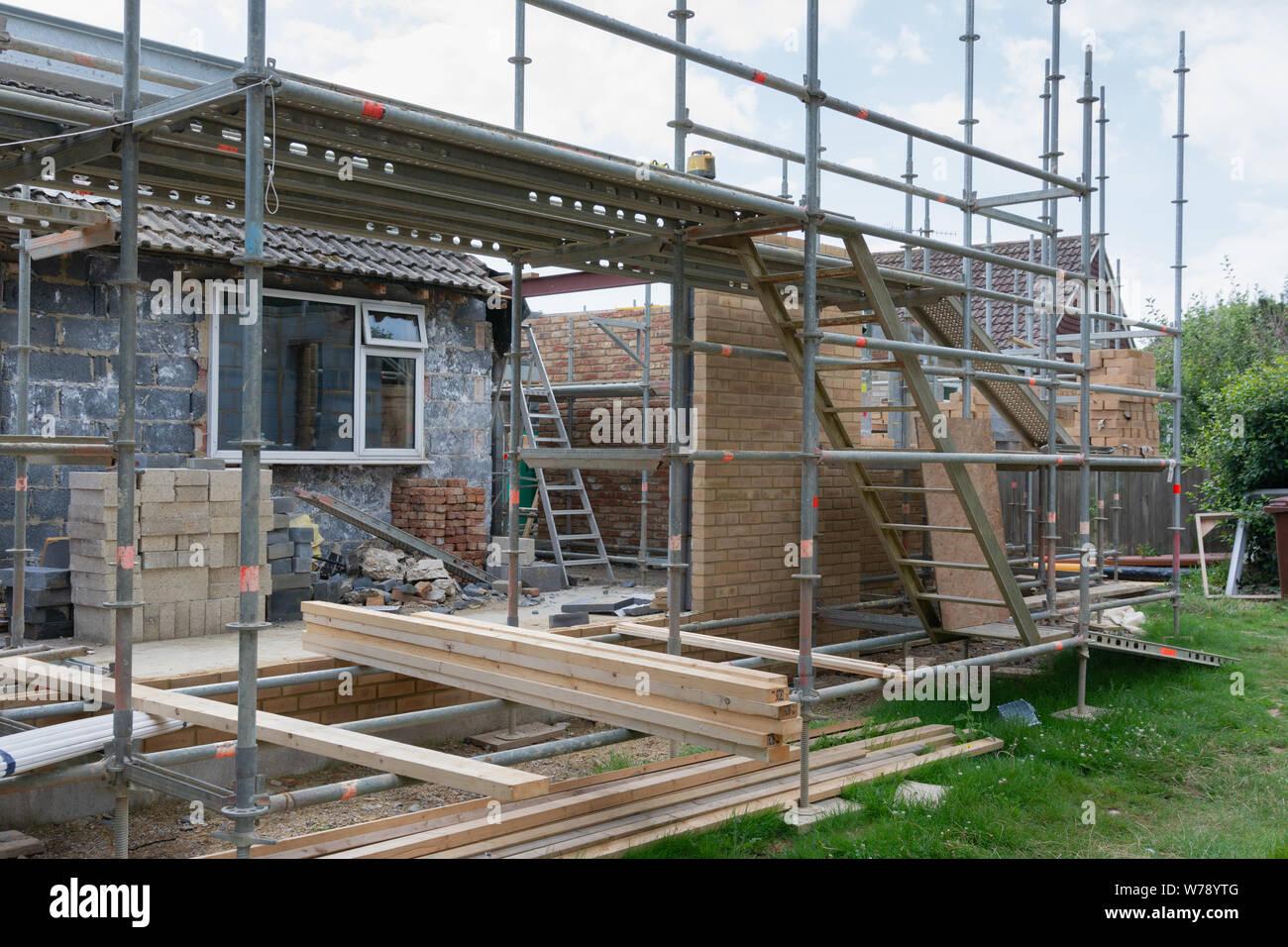 Les projets de rénovation. Construction d'extension de la maison existante, les murs de briques, inachevé, en isolement, des piles de documents sur scaffoliding, Banque D'Images
