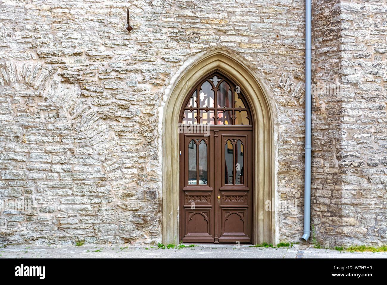 La porte en bois brun avec des vitraux en arc sur l'arrière-plan d'un mur de pierre. À partir d'une série de portes sur le monde. Banque D'Images