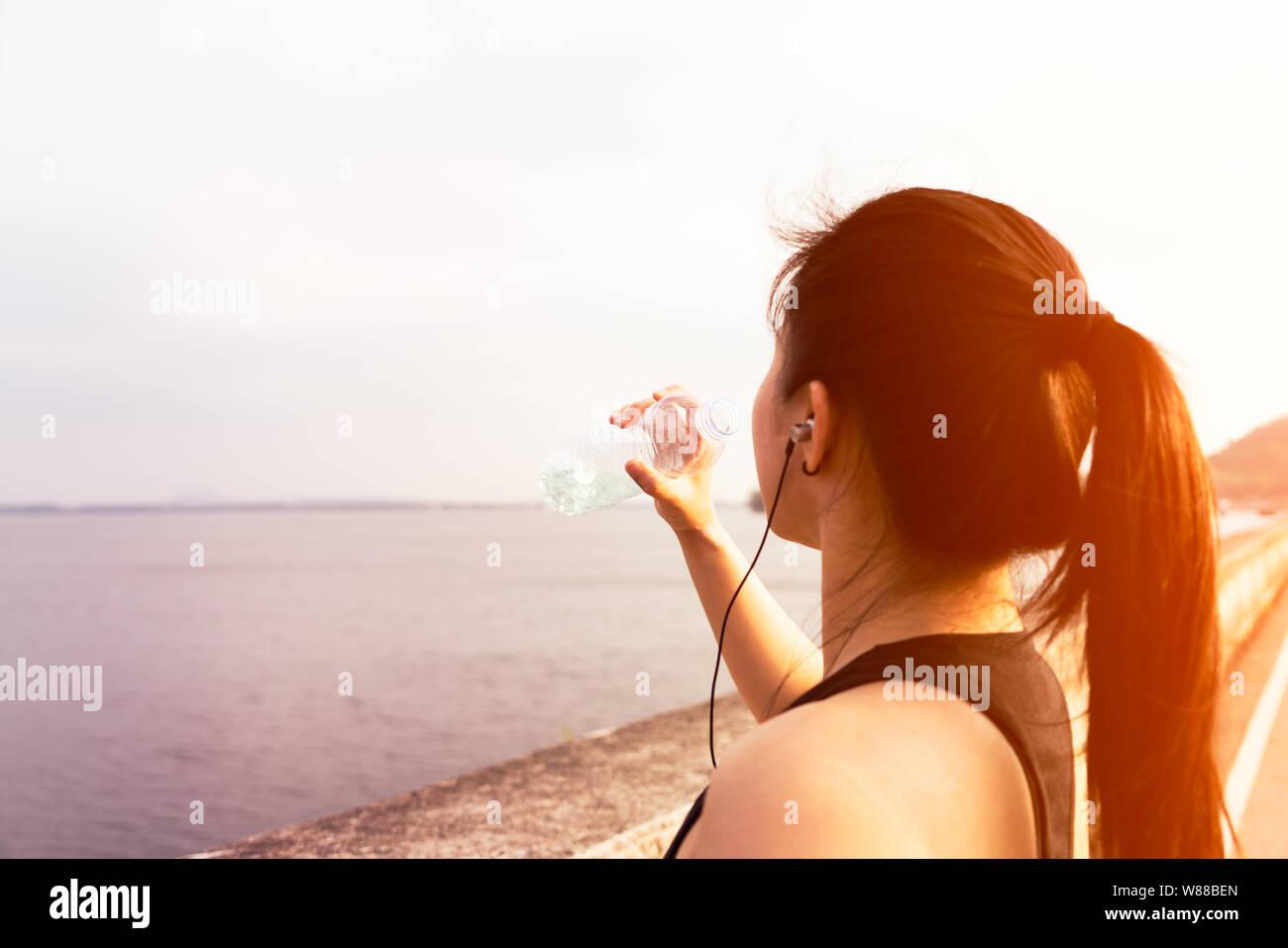 Sport femme debout sur la baie et l'eau potable après l'exécution Banque D'Images