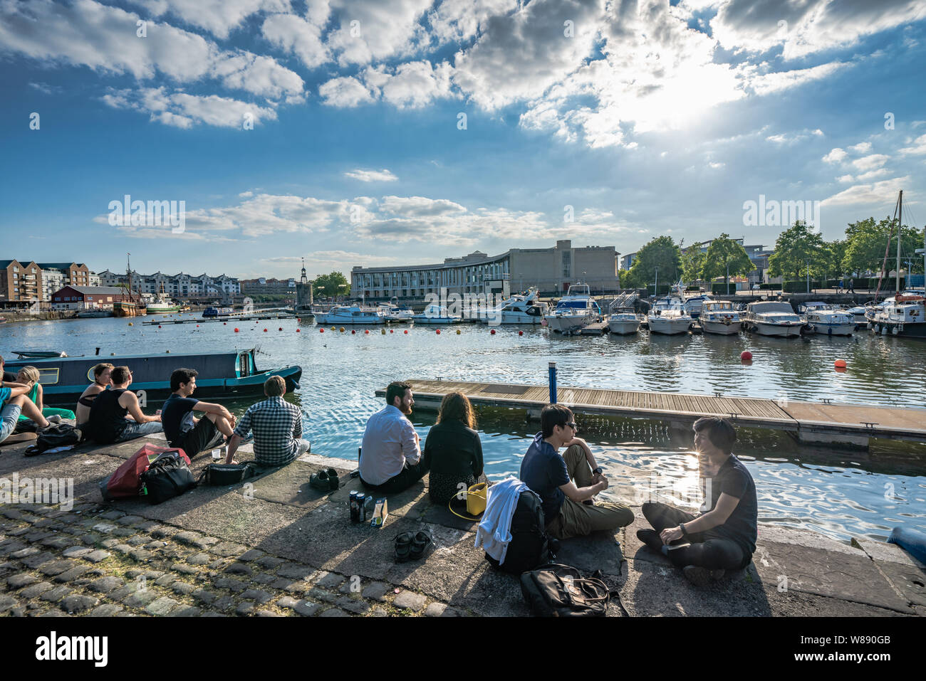 Les gens assis au bord de la rivière de la zone portuaire de Bristol Banque D'Images