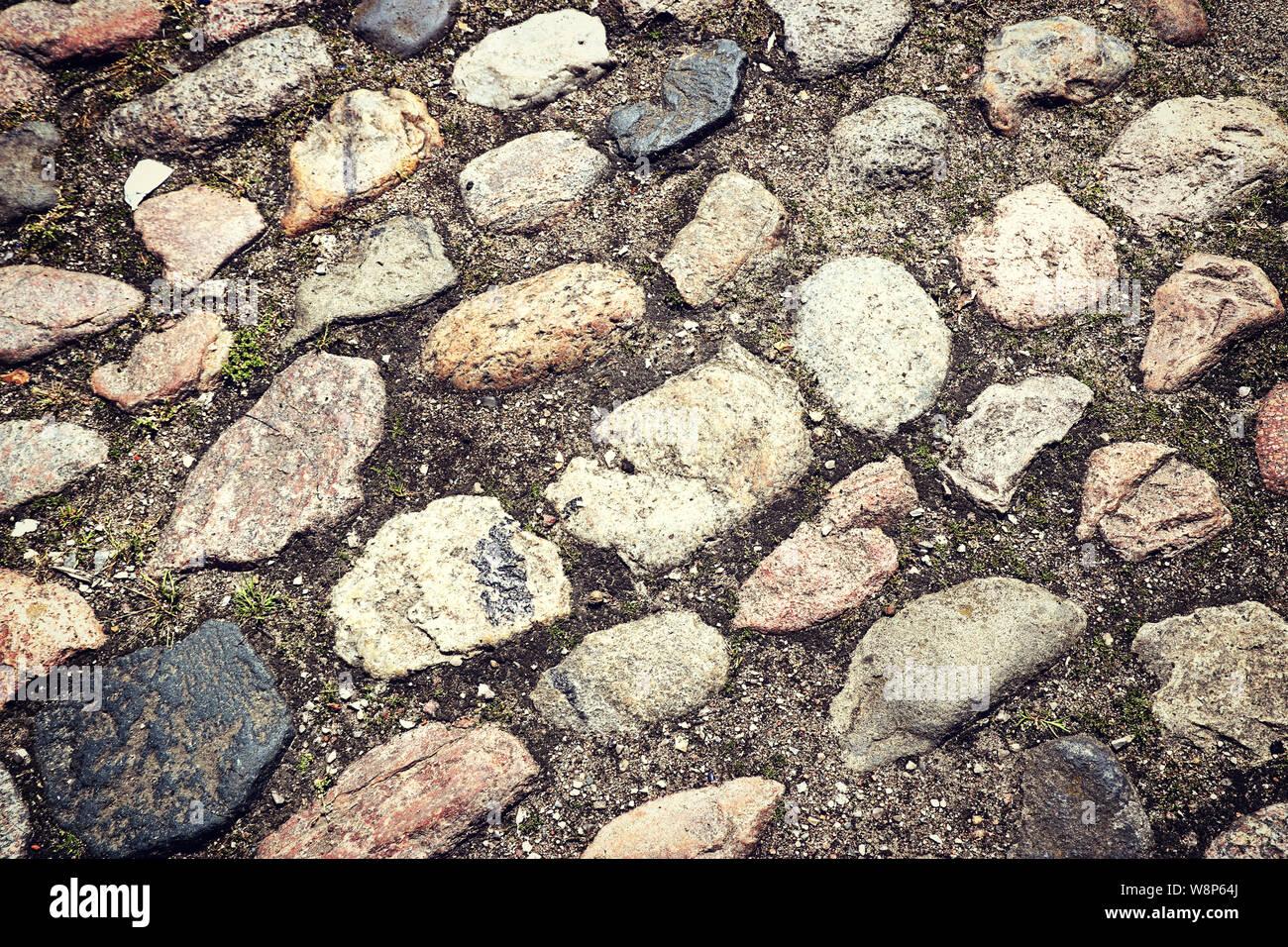 La chaussée de la rue antique faite de pierres dans le sol nivelé Banque D'Images