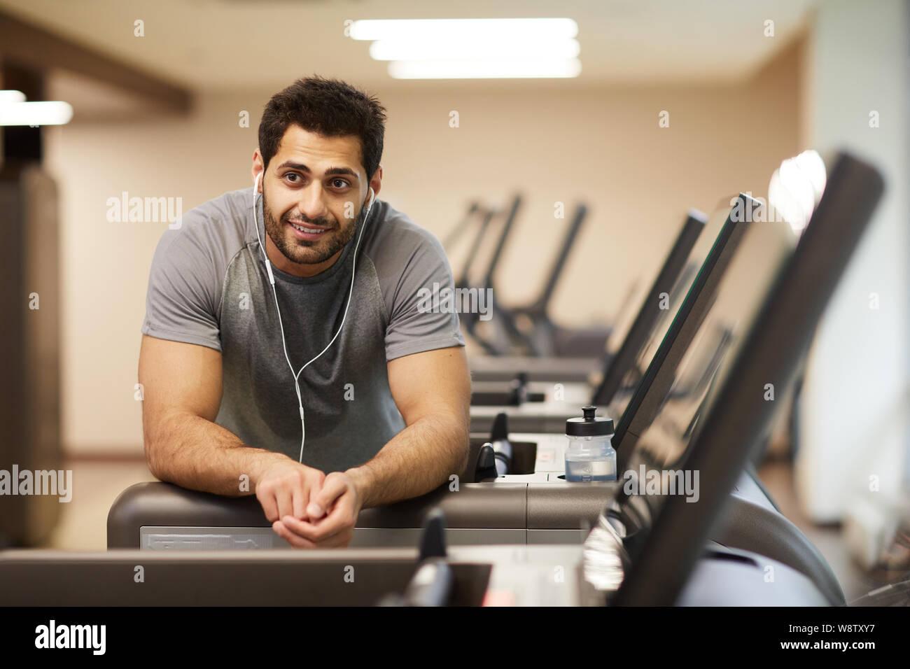 Portrait de l'homme musclé en pause de l'exercice dans la salle de sport et à l'écoute de musique, copy space Banque D'Images