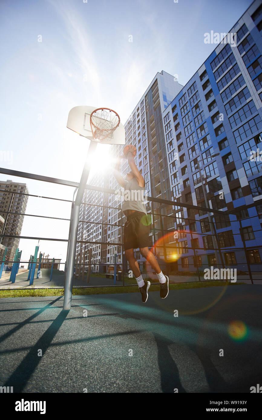 Photo d'action de tir de basket-ball africain slam dunk en cour de plein air, lens flare Banque D'Images