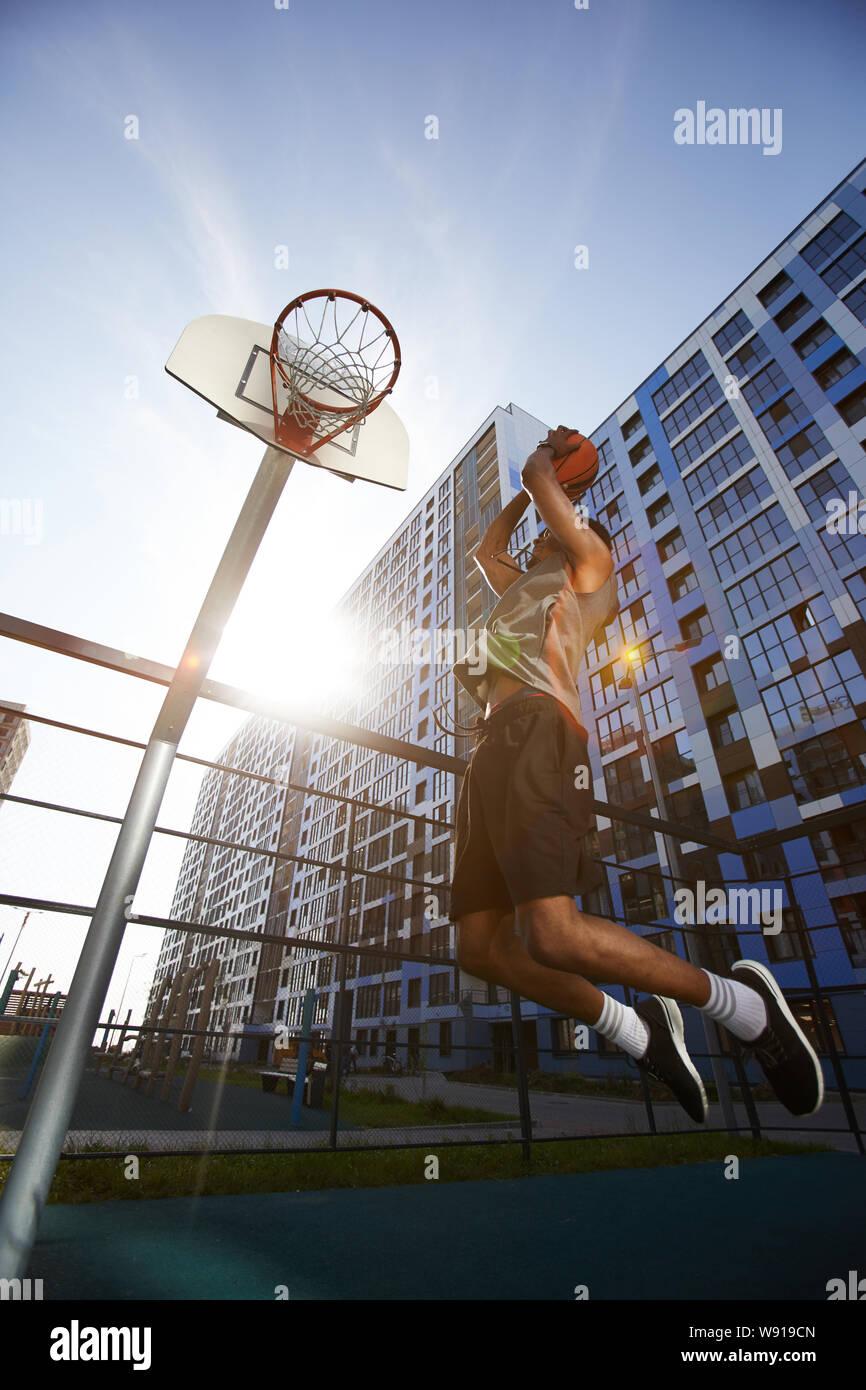 Low angle photo d'action de tir de basket-ball africain slam dunk en cour de plein air, copy space Banque D'Images