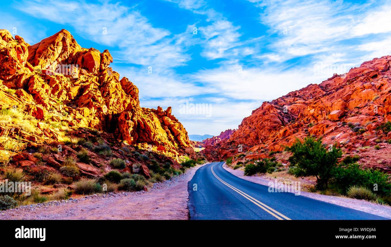 Le lever du soleil sur le rocher de grès Aztec rouge vif le long du réservoir formations souris route qui serpente à travers le parc national de la Vallée de Feu au Nevada, USA Banque D'Images