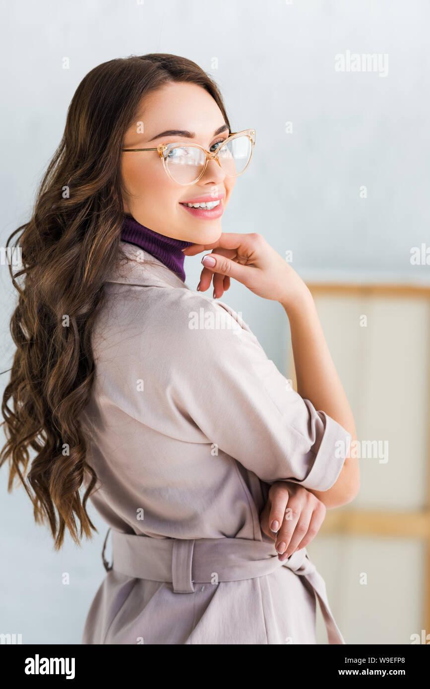 Belle jeune femme dans les verres smiling while looking at camera Banque D'Images