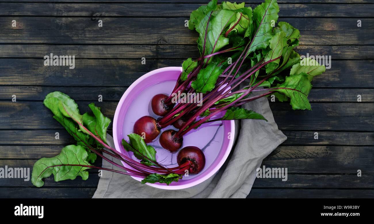 Betteraves en rinçant. betterave est un helthy et alimentaire est riche en antioxydants et vitamines. Racines dans une cuvette d'eau sur une table en bois sombre. Banque D'Images