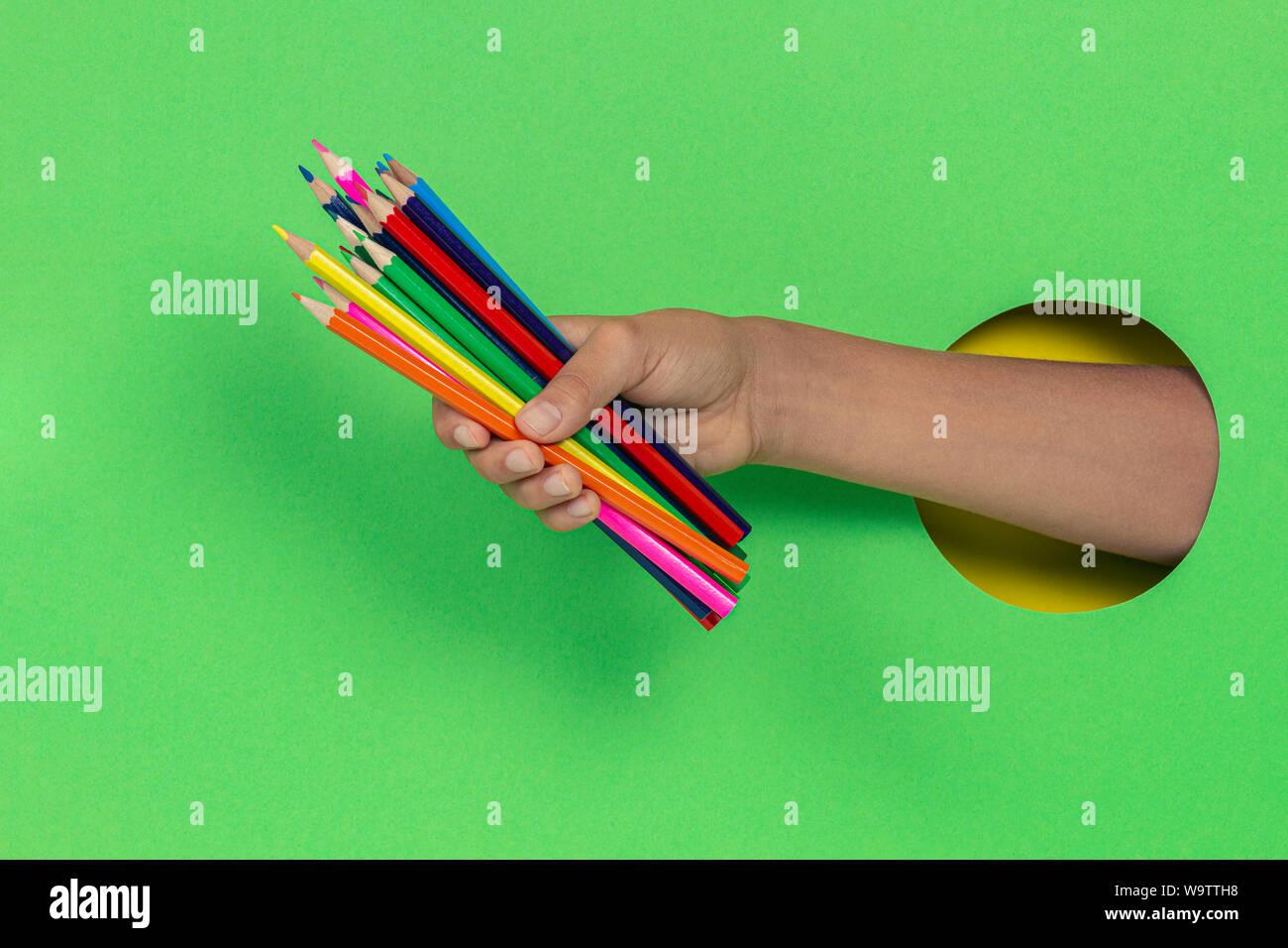 Kid holding crayons de couleur dans la main à travers le trou à fond vert clair Banque D'Images