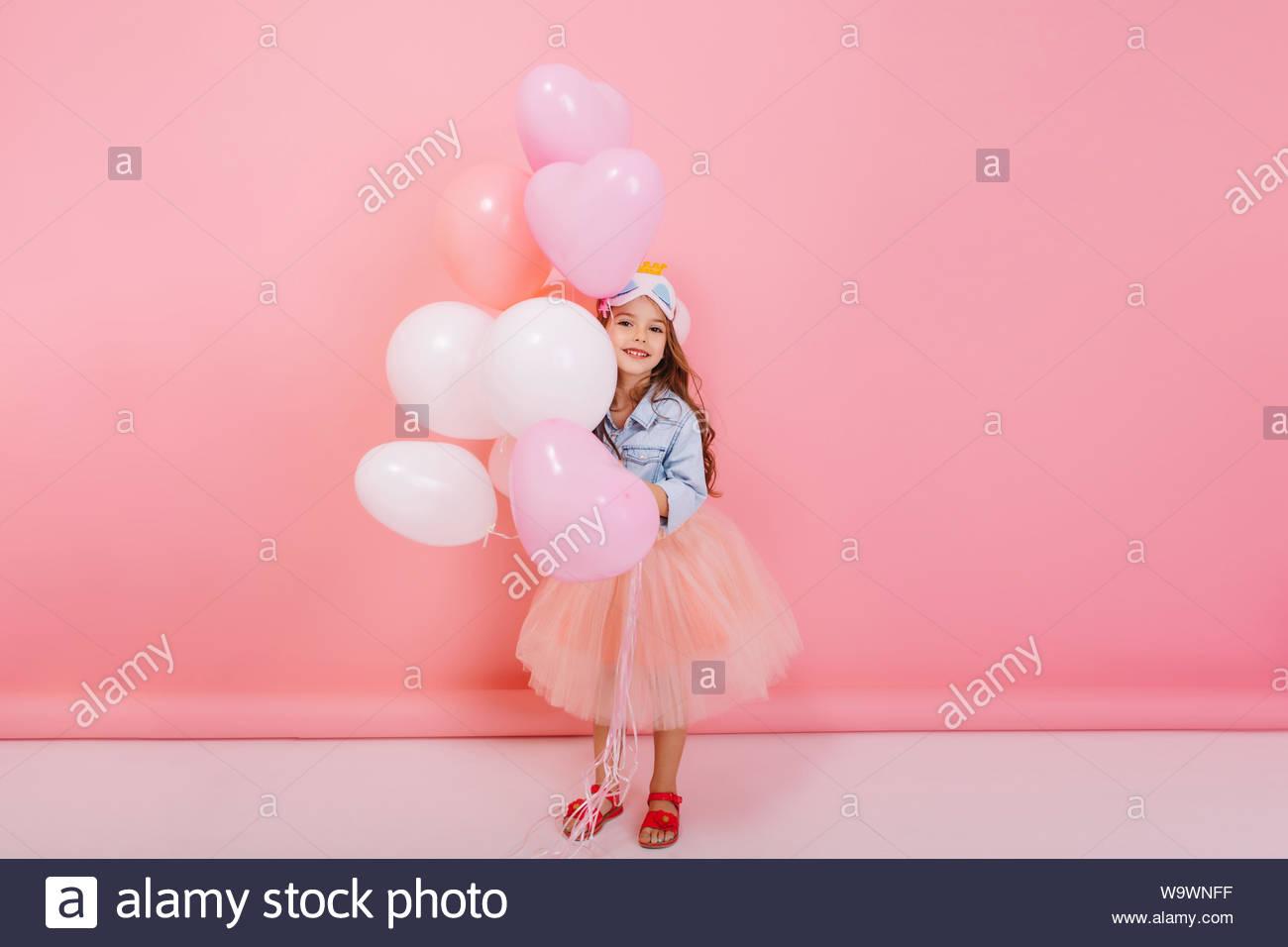 Petite fille joyeuse à tulle jupe smiling to camera, s'amusant avec des ballons sur fond rose. Avoir de l'humeur d'anniversaire enfant très élégant, Outlook, l'expression de positivité Banque D'Images