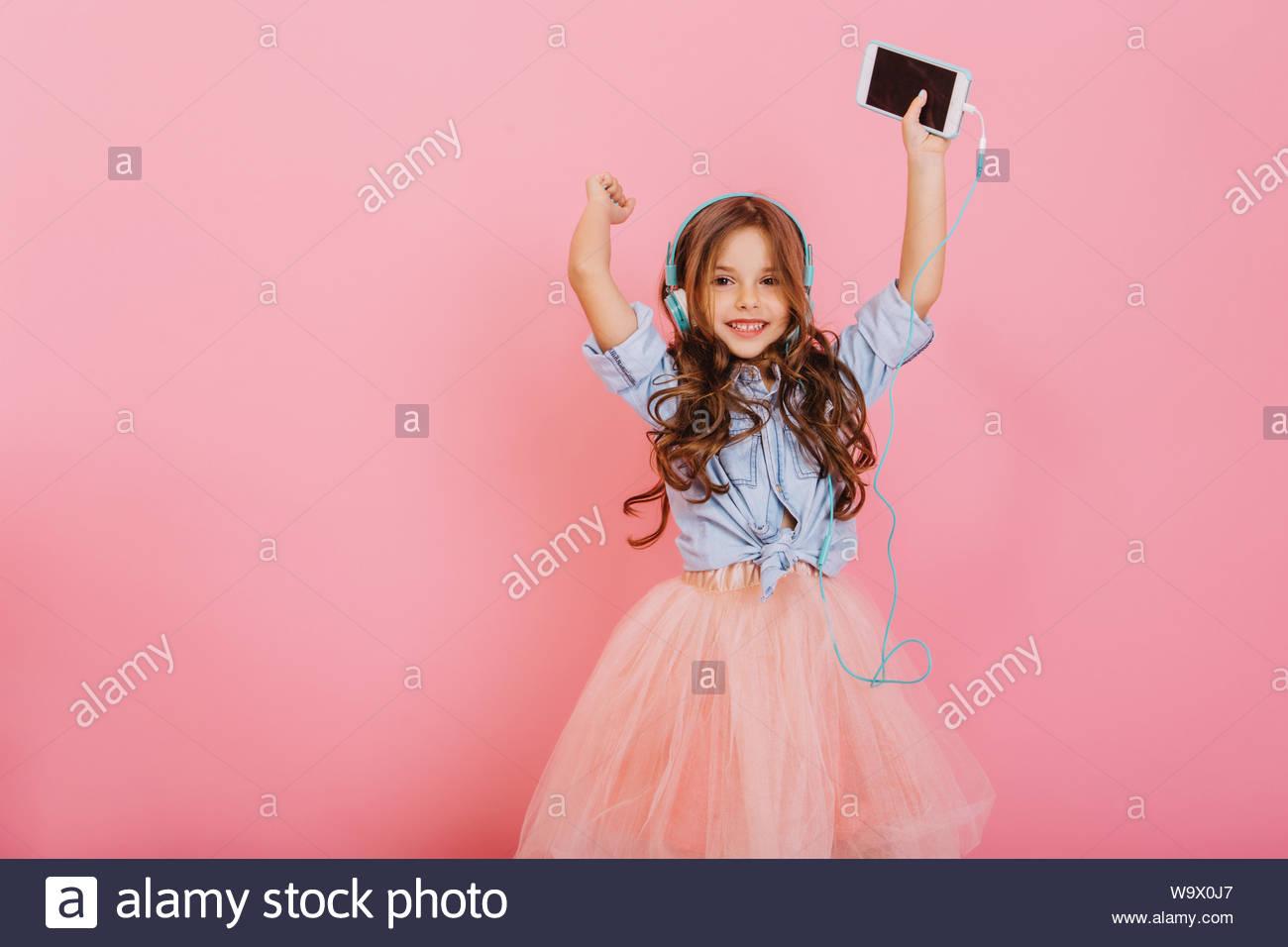 Avoir du plaisir, l'expression vraie des émotions positives de joie incroyable jeune fille l'écoute de musique au casque isolé sur fond rose. Enfance heureuse de cute kid. Place pour le texte Banque D'Images