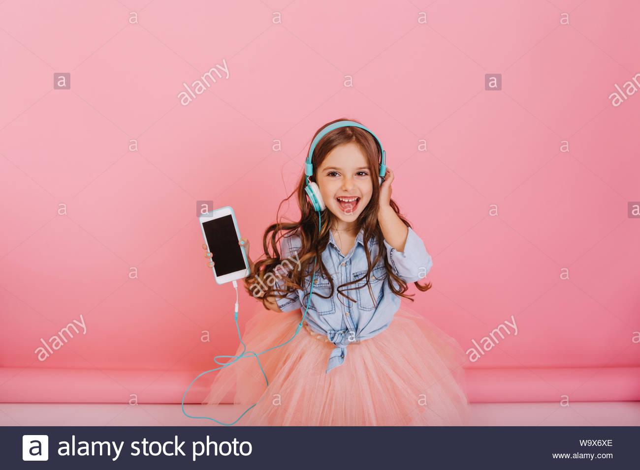 Amazing little girl joyeux à tulle jupe d'écouter de la musique via un casque bleu isolé sur fond rose. Exprimer ses émotions à la caméra brightful, bénéficiant d'une belle chanson Banque D'Images