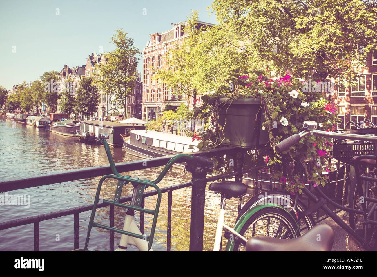 Amsterdam avec des vélos sur le pont sur un canal avec filtre de tonalité vintage. Banque D'Images