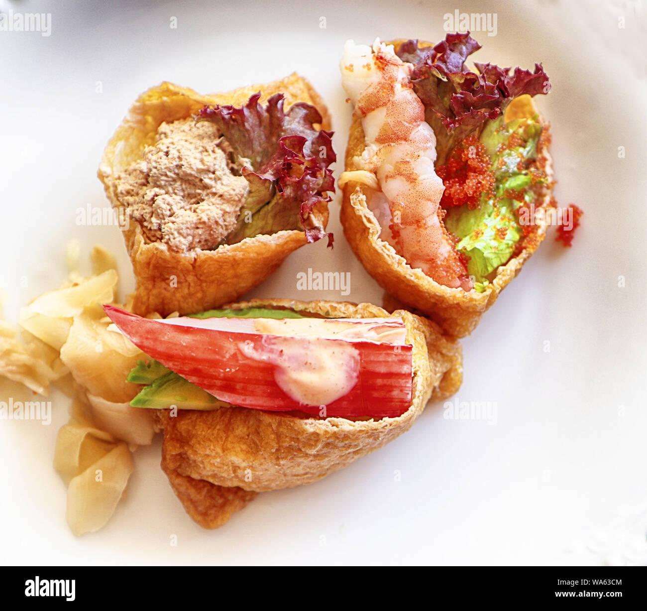 Assortiment de Sushi sur fond blanc: avocat, crevettes,le gingembre,rouge,concombre,caviar rouge Banque D'Images