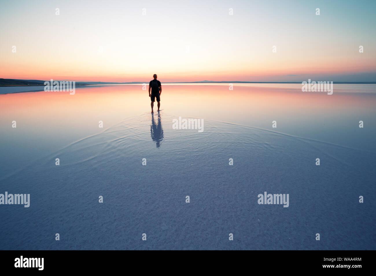 Silhouette of man au départ dans le coucher du soleil sur l'eau lisse du lac Banque D'Images