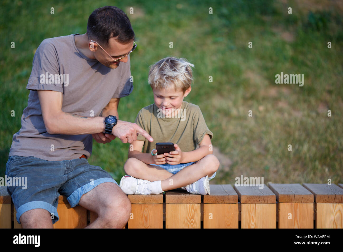 Image de l'homme heureux et garçon avec des téléphones portables dans les mains, assis derrière une clôture en bois park Banque D'Images