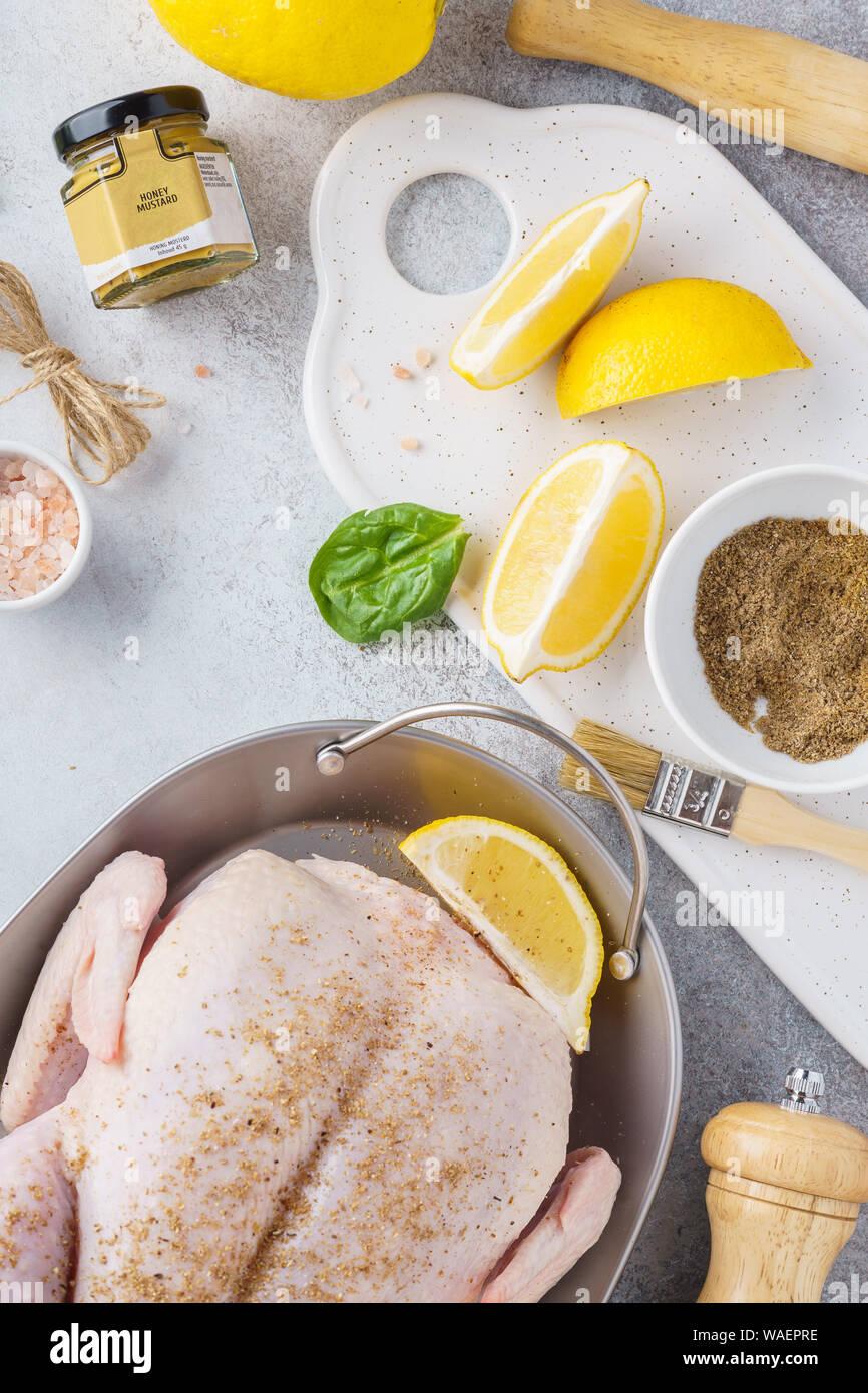 La préparation de la Turquie ou de poulet farcis pour un dîner de célébration festive. Poulet cru avec des herbes, épices, citron et moutarde au miel. Banque D'Images