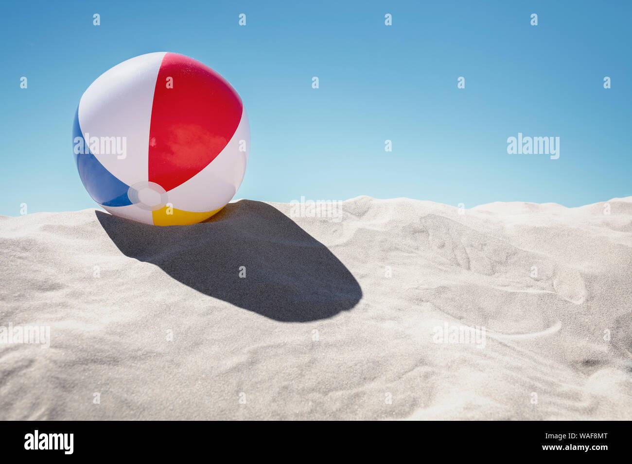 Beach ball resting in sand dune concept pour les vacances d'enfance, des vacances en famille et mode de vie sain Banque D'Images