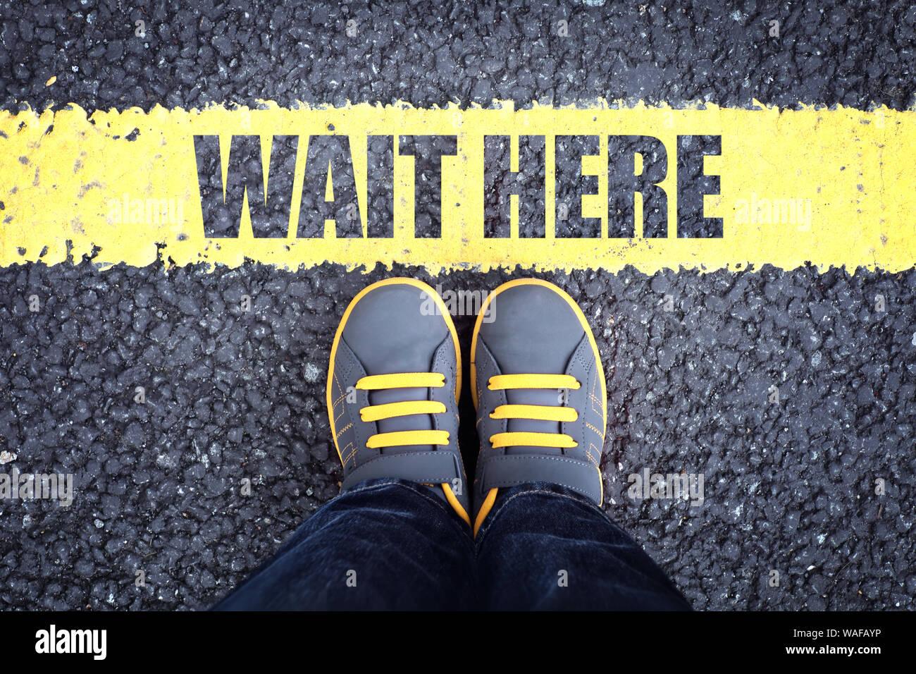 Attendre ici pieds derrière la file d'attente jaune Banque D'Images