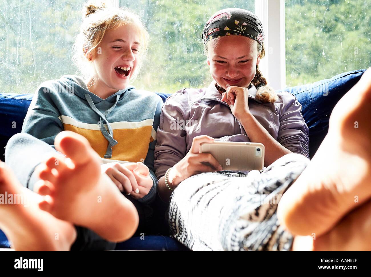 Les jeunes filles assis sur un canapé en regardant un écran et de rire Banque D'Images