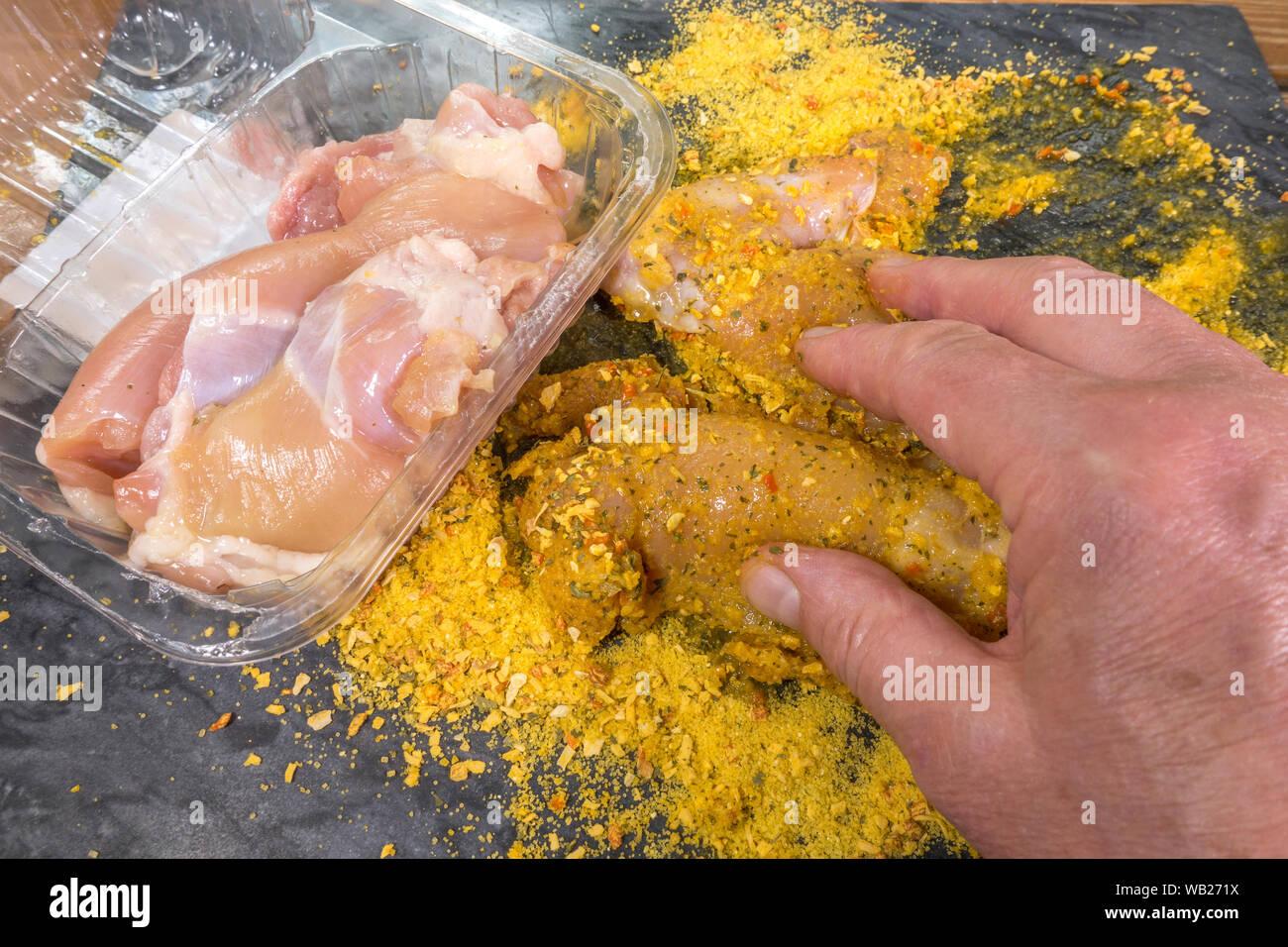Près d'un coup de frais généraux entre les mains de l'homme des morceaux de revêtement le poulet cru avec un mélange d'assaisonnement sec, prêt pour la cuisson. Banque D'Images