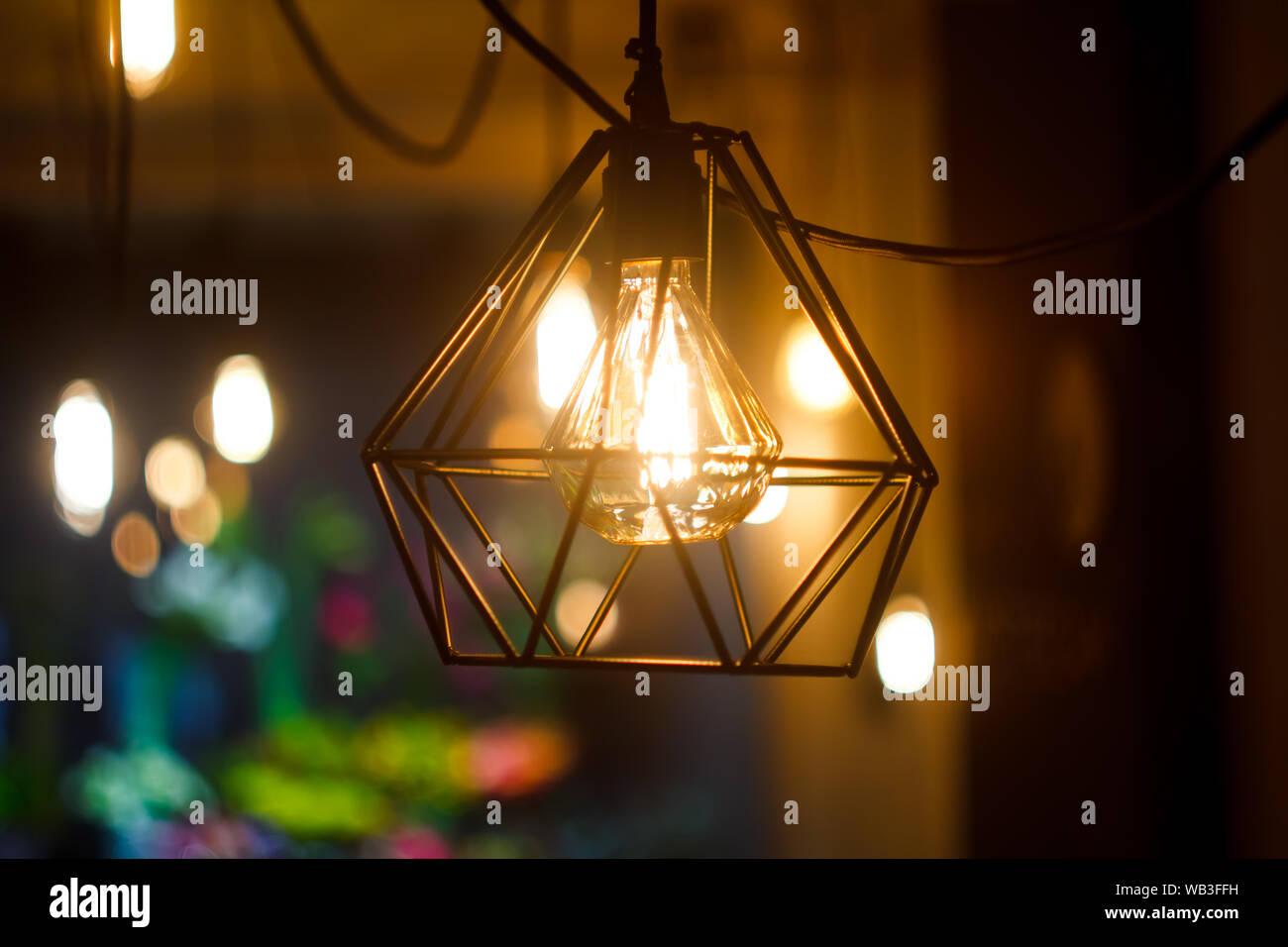 Close up vintage retro sphérique suspendu lumineux ampoule à incandescence d'Edison en metal abat-jour contre l'arrière-plan de floue d'autres feux, sélective focu Banque D'Images