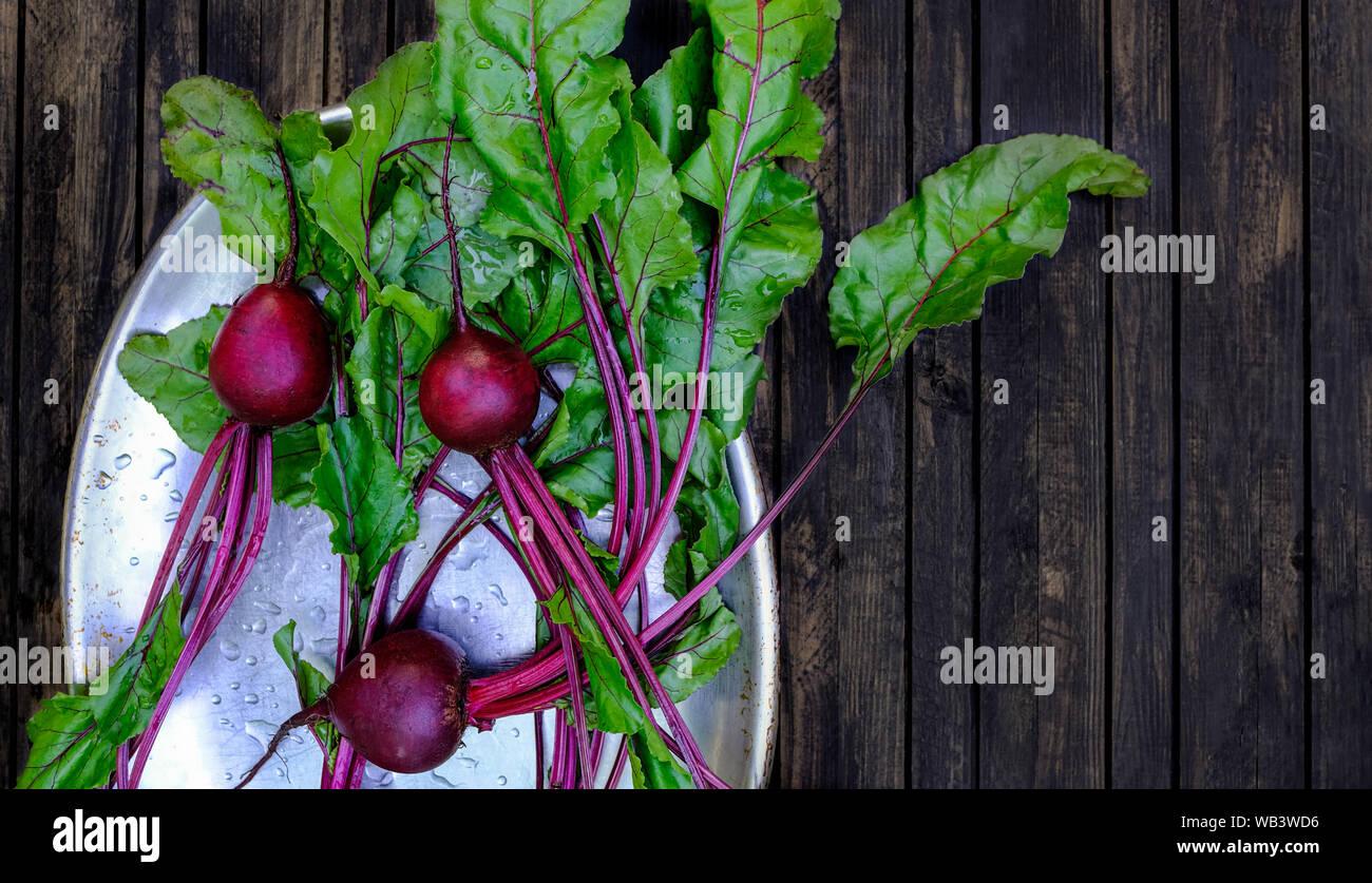 Betteraves fraîches sur une table en bois sombre arrière-plan. Nettoyer les légumes lavés sur une plaque de métal Banque D'Images