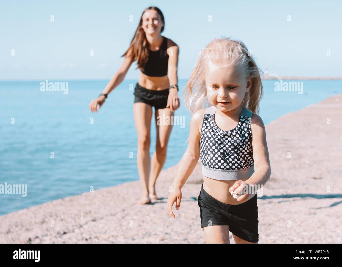 Petite fille mignonne à monter à la maman sur plage, bonne hygiène de vie, sport famille Banque D'Images