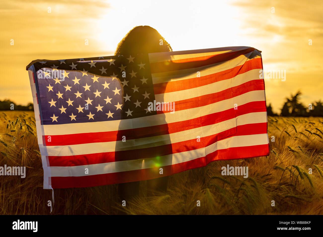 Mixed Race African American girl adolescent femme jeune femme dans un champ de blé ou d'orge enveloppés dans USA stars and stripes flag au coucher du soleil Banque D'Images