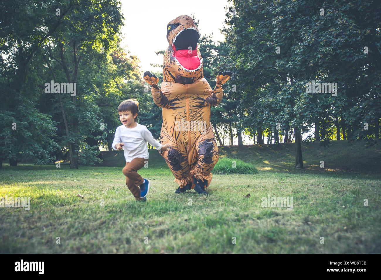 Père et fils à jouer au parc, avec un costume de dinosaure, s'amusant avec la famille piscine Banque D'Images