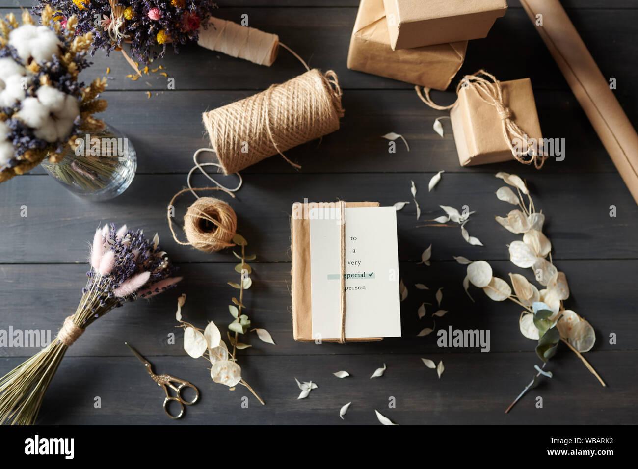 Voir ci-dessus des cadeaux emballés sur table avec des pétales en désordre Banque D'Images