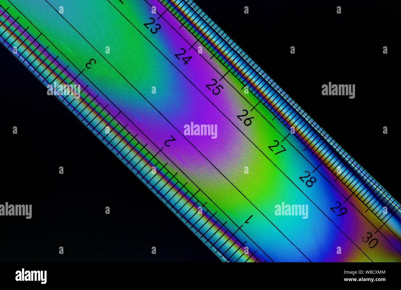 Image de polarisation croisée une règle indiquant les motifs colorés dans le plastique du stress Banque D'Images