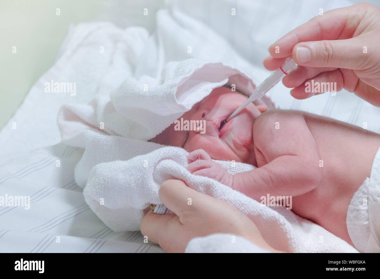 Les mains coupées de médecin d'administrer un médicament à bébé garçon sur le lit Banque D'Images