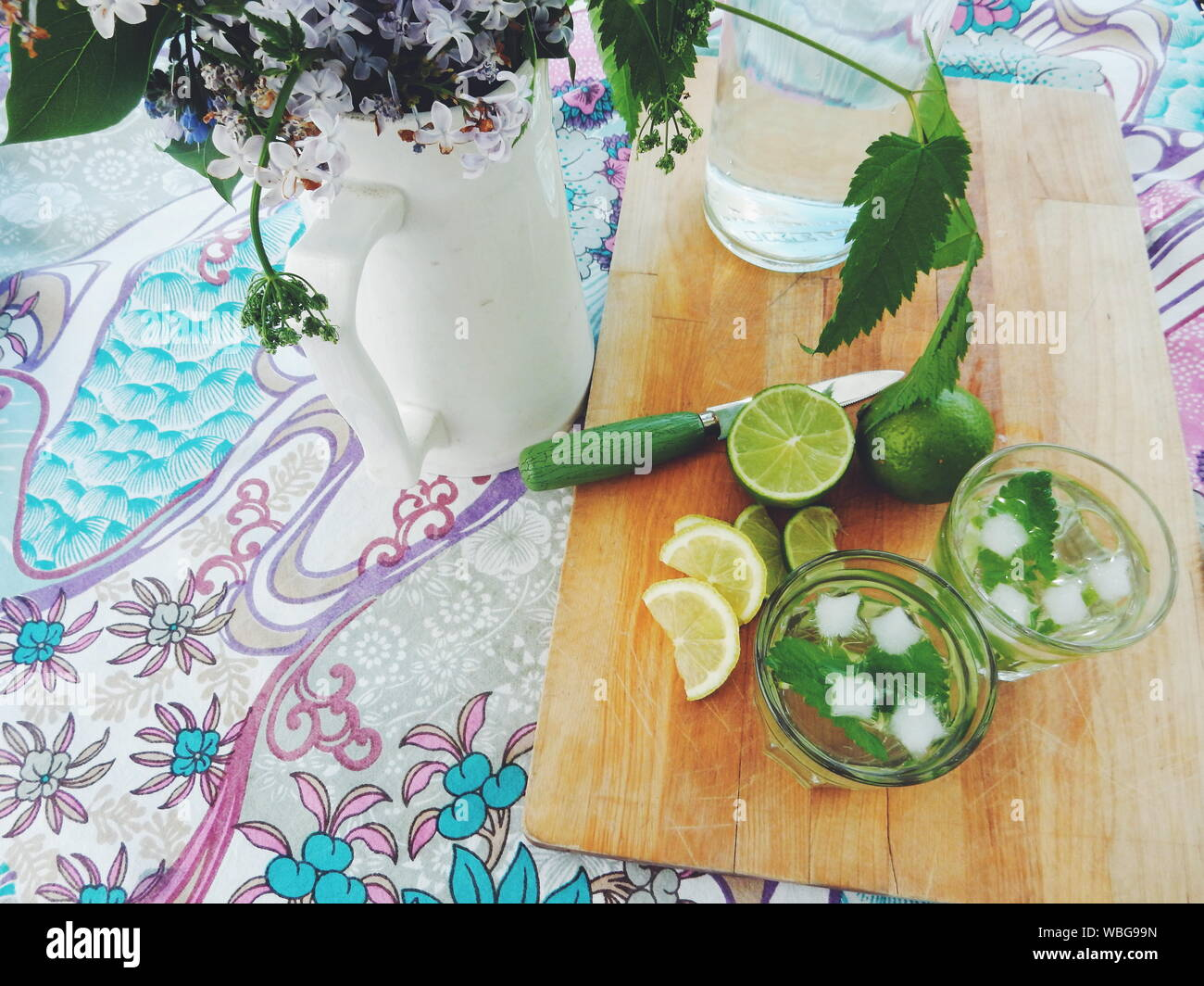 Portrait de Mojito sur une planche à découper par Vase à fleurs sur table Banque D'Images