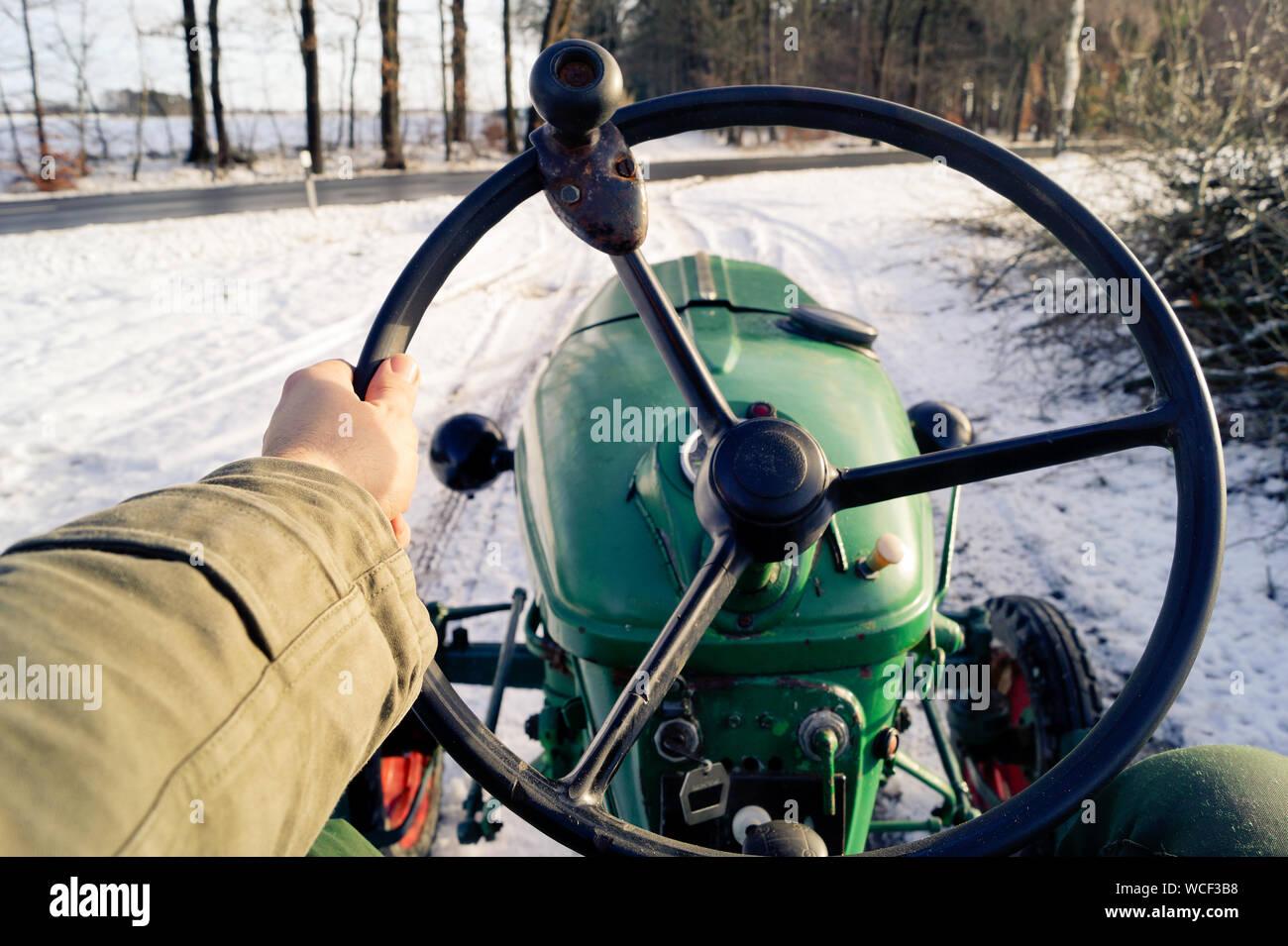 Portrait de la personne conduisant le tracteur sur la route couverte de neige pendant l'hiver Banque D'Images