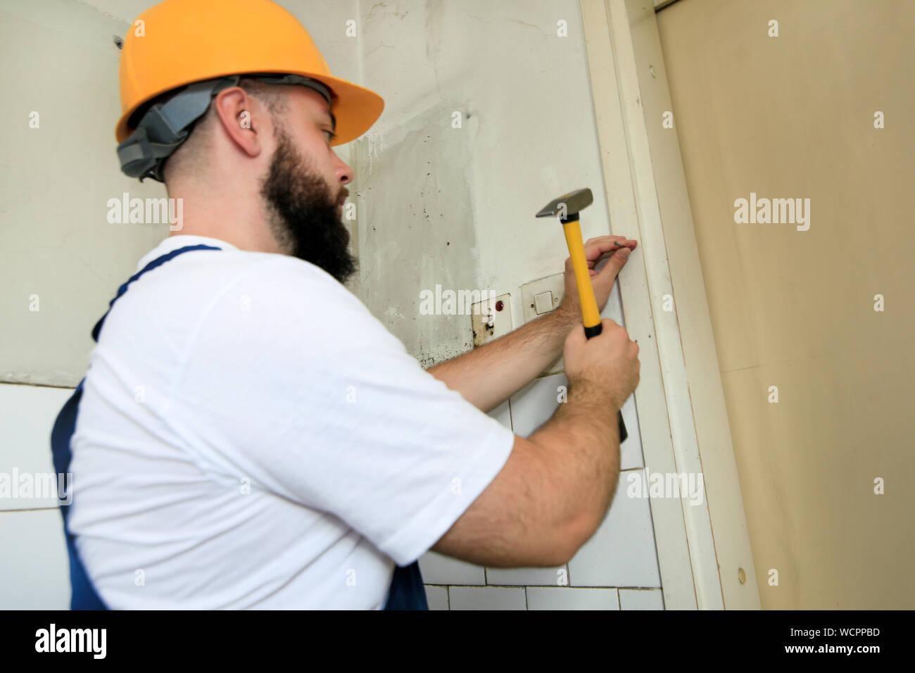 Travailleur de la construction et l'homme à travailler sur des travaux de rénovation. Builder avec marteau frappe jaune et des ongles un clou dans le mur en bois de porte de la cuisine. Banque D'Images