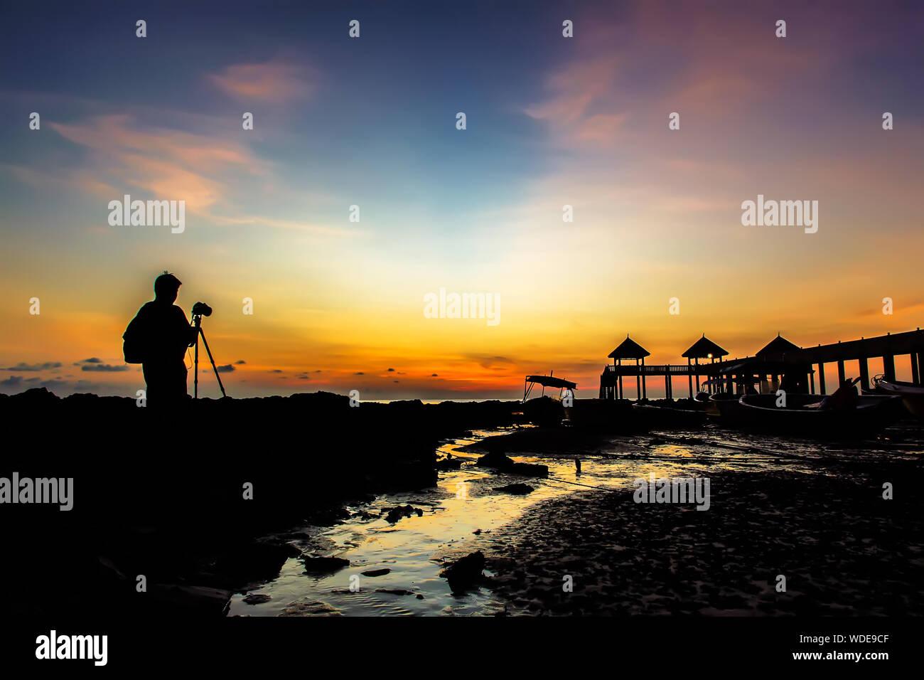 Silhouette Of Man avec l'équipement de l'appareil photo sur la plage au coucher du soleil Banque D'Images
