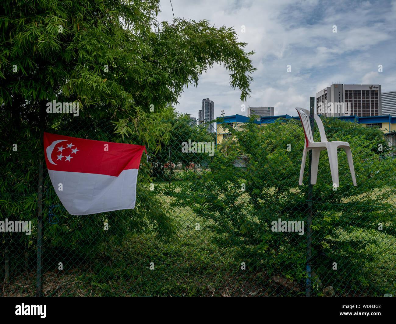 Drapeau singapourien Hanging On clôture avec Ville en arrière-plan Banque D'Images