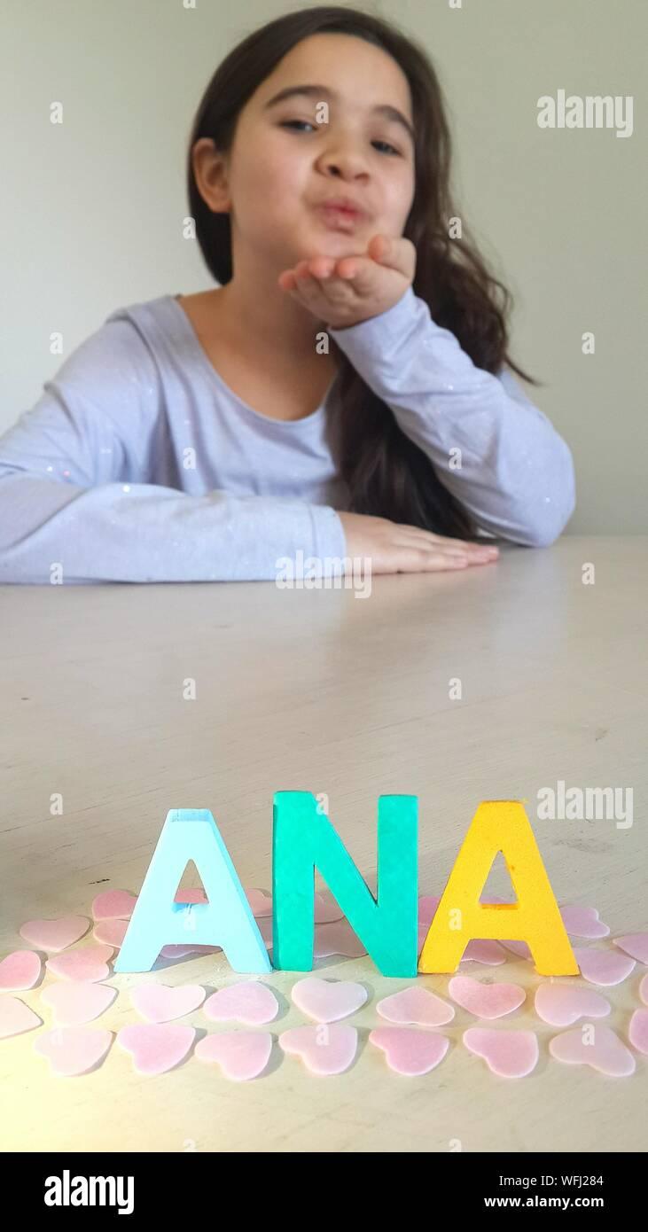 Portrait Of cute girl Blowing Kiss vers l'alphabet sur le tableau à la maison Banque D'Images